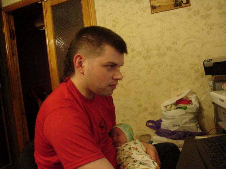 Сергей работает за компьютером с новорожденной дочкой на руках